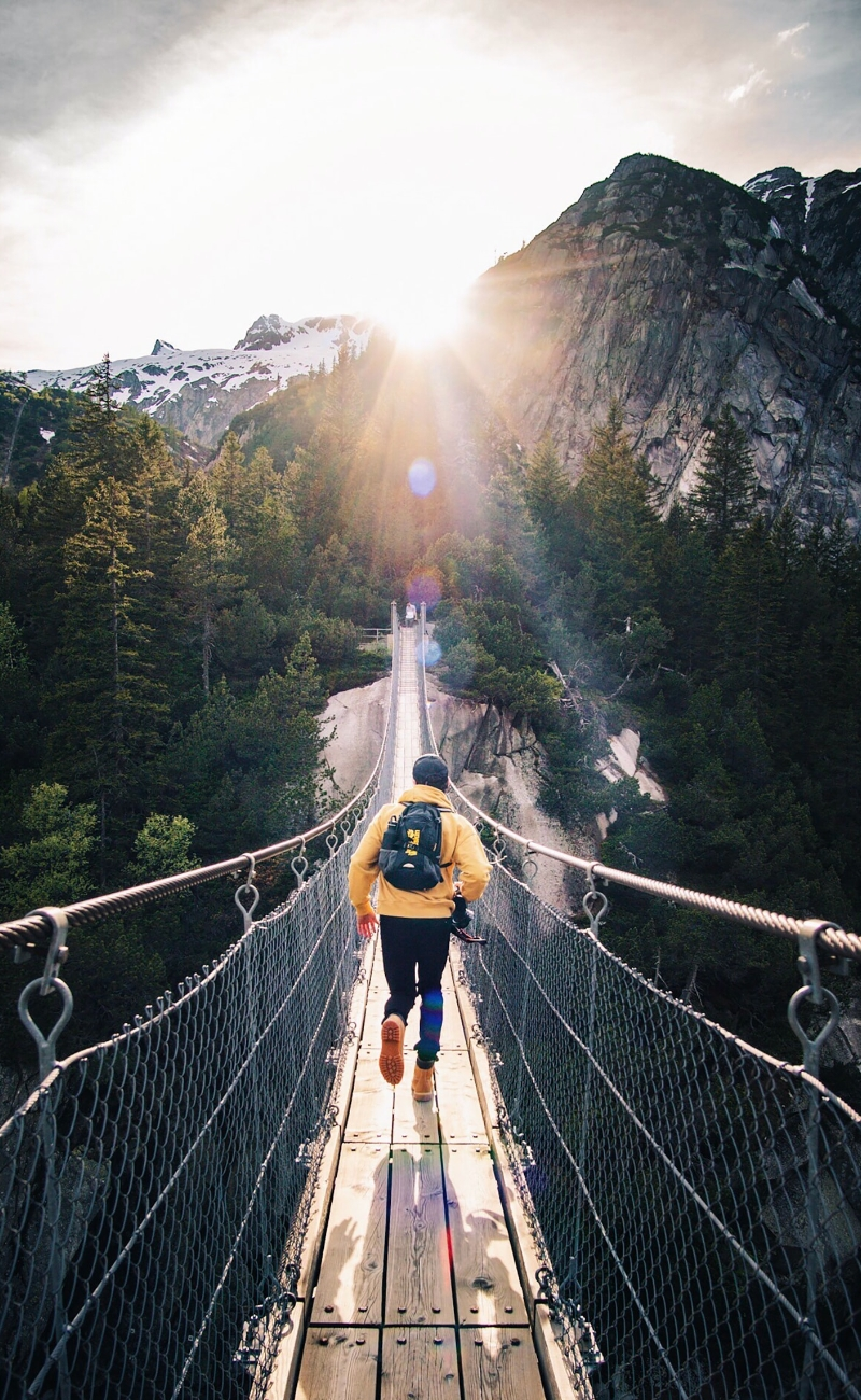 hiker crossing bridge